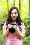 自然摄影师盖子的画象他的有面孔的照相机屏幕在春天公园庭院森林里 免版税库存图片