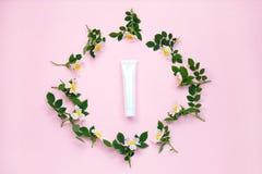 自然有机化妆包装假装与在粉红彩笔背景的花 烙记和标签的大模型瓶 库存照片