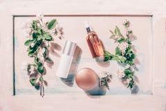 自然有机化妆用品:血清,奶油,在木背景的面具与花 Skincare概念 免版税库存图片
