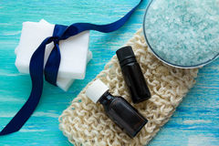 自然有机肥皂装瓶在一张蓝色木桌上的精油和海盐有机丝瓜络 库存照片