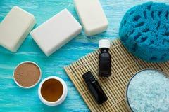 自然有机肥皂装瓶在一张蓝色木桌上的精油和海盐草本浴 免版税图库摄影