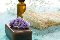 自然有机肥皂装瓶在一张蓝色木桌上的精油和海盐草本浴 免版税库存照片