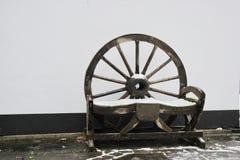 自然木轮子车顶上的座位/长凳在白色的雪黑,棕色和 库存照片