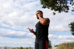 自然本底的一位性感的运动员 听到一些音乐的一位肌肉慢跑者户外 体育,音乐概念 库存照片