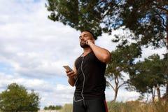 自然本底的一位性感的运动员 听到一些音乐的一位肌肉慢跑者户外 体育,音乐概念 免版税库存图片
