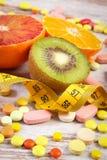 自然果子、厘米和医疗药片,减肥,选择在健康营养和医疗补充之间 免版税图库摄影