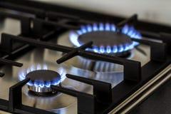 自然气体燃烧在厨房在黑暗的煤气炉 从钢的盘区与在黑背景的一台小煤气炉燃烧器,特写镜头赶走 免版税库存图片