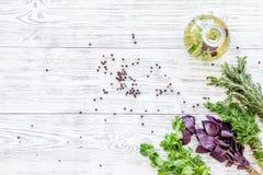 自然油和新鲜的绿叶烹调在木厨房用桌背景顶视图空间的餐馆的文本的 免版税库存图片