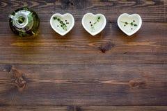 自然油和新鲜的绿叶烹调在木厨房用桌背景顶视图空间的餐馆的文本的 图库摄影