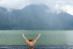 自然游泳池的资深妇女有惊人的山背景 热带海岛巴厘岛,印度尼西亚 免版税图库摄影