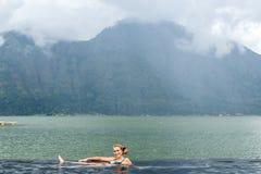 自然游泳池的资深妇女有惊人的山背景 热带海岛巴厘岛,印度尼西亚 库存图片