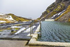 自然游泳池Seljavallalaug在有人的冰岛在水中和多雪的天气和山所有 免版税图库摄影
