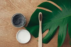 自然牙膏在木背景的活性炭和竹牙刷与绿色monstera叶子 塑料自由秀丽 免版税库存照片