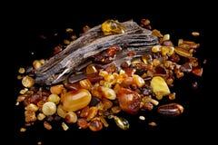 E 自然琥珀不同颜色许多片断在扔石头的木头大片断的  库存照片