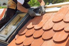 自然瓦instaalation 盖屋顶的人建造者工作者测量瓦片之间的距离的用途ruller 有有双重斜坡屋顶的房屋wi的屋顶 免版税库存照片