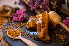 自然甜蜂窝和花粉在桌上 库存图片