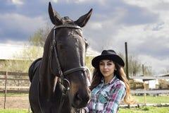 自然的一个女孩在一匹黑马旁边 免版税图库摄影