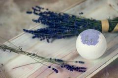 自然的化妆用品 手工制造淡紫色浴炸弹、淡紫色花和毛巾在白色木板条,顶视图 库存图片