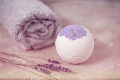 自然的化妆用品 手工制造淡紫色浴炸弹、淡紫色花和毛巾在白色木板条,顶视图 免版税图库摄影