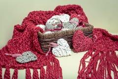 自然羊毛被编织的红色围巾 以球的形式圣诞节装饰和心形 免版税库存图片