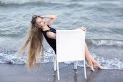 自然蓝色海背景的一个惊人的女孩 一件皮包骨头的黑礼服的一个热的夫人 在椅子的时髦的女性开会 免版税图库摄影