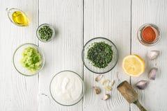 自然酸奶和另外调味料在白色木台式视图 库存图片