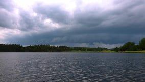 自然风景出色的意见在日落的 用重的雷雨云盖的天空 与小水波纹的镜子表面 股票视频