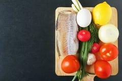 自然食物的成份从成熟蕃茄、葱、大蒜、柠檬、萝卜、鸡蛋和鱼肉 有机粮食 顶视图 免版税库存照片