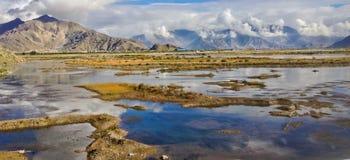 自然高原美丽的景色与明亮的天天空背景的沼泽、小河和水反射的 风景旅行向西藏 图库摄影