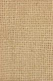 自然织地不很细粗麻布麻袋布黑森州的纹理咖啡大袋,轻的国家袋装的帆布,垂直的宏观背景样式 免版税库存照片