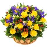 自然黄色玫瑰和蓝色虹膜在篮子 库存照片