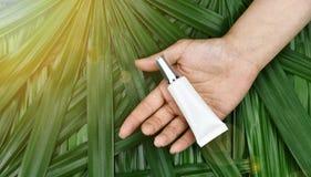 自然skincare美容品概念,化妆瓶容器在手中在绿色草本叶子背景 免版税库存照片