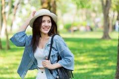 自由和发现概念:走在公园的偶然逗人喜爱的聪明的亚裔妇女 免版税库存照片