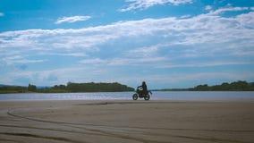 自由和Moto美学的感觉 在他的自行车的摩托车骑士骑马在沙滩 股票视频