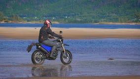 自由和Moto美学的感觉 在他的自行车的摩托车骑士骑马在沙滩 股票录像