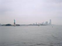 自由女神像和泽西市在一多云天 库存图片