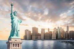 自由女神像有更低的曼哈顿背景在日落,纽约地标的晚上  免版税库存图片