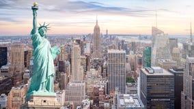自由女神像有曼哈顿地平线背景,摩天大楼鸟瞰图在日落的纽约在晚上 库存图片