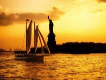 自由女神像的剪影和在日落的一条风船 免版税库存照片