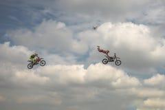 自由式摩托车越野赛把戏两名摩托车骑士头翻转蓝色云彩天空的背景的 德语Stuntdays,策尔布斯特- 2017年, 免版税库存图片
