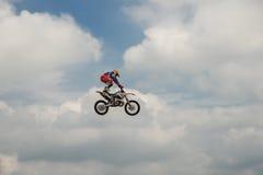 自由式摩托车越野赛车手执行与摩托车的一个把戏在蓝色云彩天空的背景 极其体育运动 德国特技 免版税库存图片