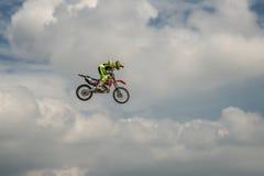 自由式摩托车越野赛车手执行与摩托车的一个把戏在蓝色云彩天空的背景 飞行在moto的天空 免版税库存照片