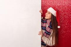 自由式 在好奇红色看的白板的年轻女人佩带的围巾和圣诞老人帽子身分 免版税库存图片