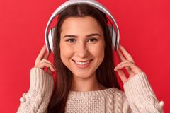 自由式 在红色听的音乐微笑耳机的年轻女人站立隔绝的暴牙对照相机特写镜头 免版税库存照片