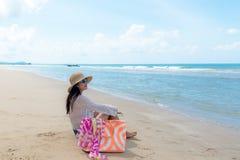 自由生活方式亚裔妇女坐看海和天空的海滩 库存图片
