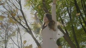 自由白色礼服投掷的叶子的少年女孩和转动用手在天空中在慢动作- 股票录像