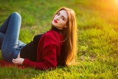 自由的愉快的少妇 有长的健康头发的美丽的女性享受太阳光的在公园在日落 春天,秋天 库存图片