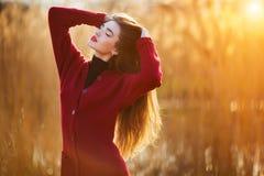 自由的愉快的少妇 有长的健康头发的美丽的女性享受太阳光的在公园在日落 春天,秋天 免版税库存图片