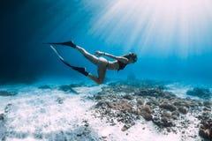 自由的潜水者滑动在有飞翅的含沙海 Freediving在蓝色海 免版税库存图片