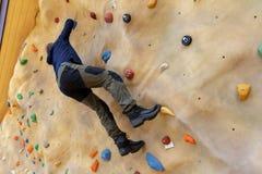 自由的登山人实践的上升在室外人为岩石墙壁上 库存照片